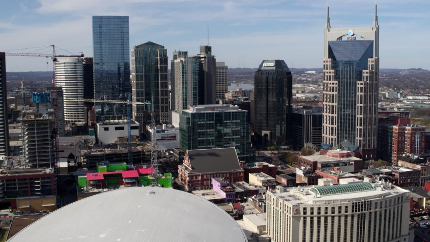 5.7K stock footage aerial video of flying away from the city's skyline, Bridgestone Arena, and Hilton hotel, Downtown Nashville, Tennessee Aerial Stock Footage | DX0002_117_048
