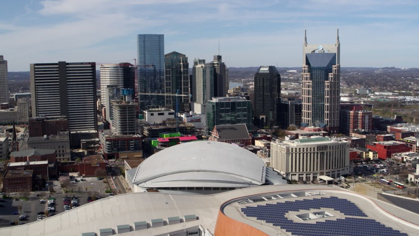 5.7K stock footage aerial video fly away from and past the city's skyline, Bridgestone Arena, and Hilton hotel, Downtown Nashville, Tennessee Aerial Stock Footage | DX0002_117_051