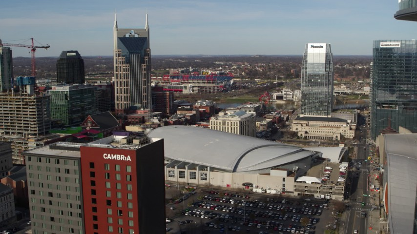 5.7K stock footage aerial video of arena between AT&T Building, Pinnacle skyscraper, descend near hotel, Downtown Nashville, Tennessee Aerial Stock Footage | DX0002_119_016
