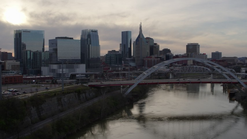 5.7K stock footage aerial video flyby bridge and river while focused on city skyline at sunset, Downtown Nashville, Tennessee Aerial Stock Footage | DX0002_119_031
