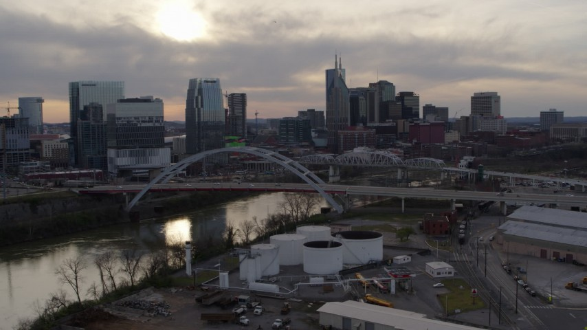 5.7K stock footage aerial video of a view of the Cumberland River, bridges, and city skyline at sunset, Downtown Nashville, Tennessee Aerial Stock Footage | DX0002_119_032