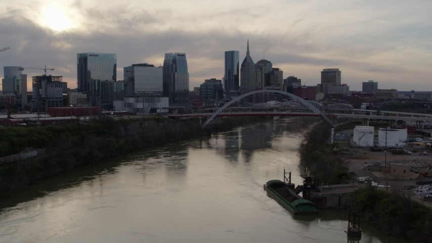 5.7K stock footage aerial video follow the river toward the bridge and city skyline at sunset, Downtown Nashville, Tennessee Aerial Stock Footage | DX0002_119_034