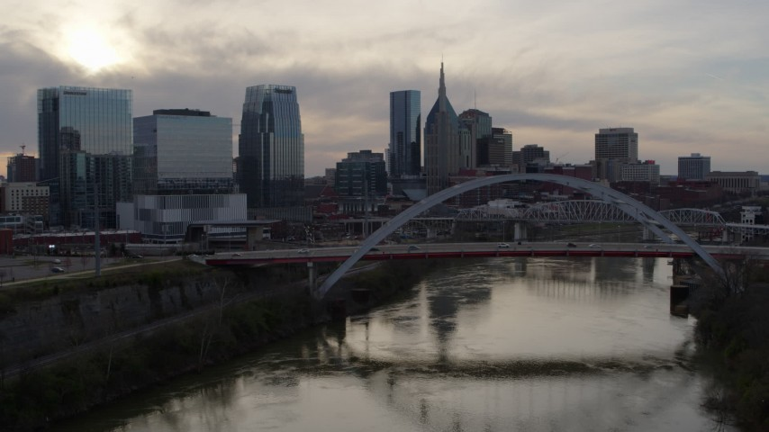 5.7K stock footage aerial video follow the river to approach the bridge and city skyline at sunset, Downtown Nashville, Tennessee Aerial Stock Footage | DX0002_119_035