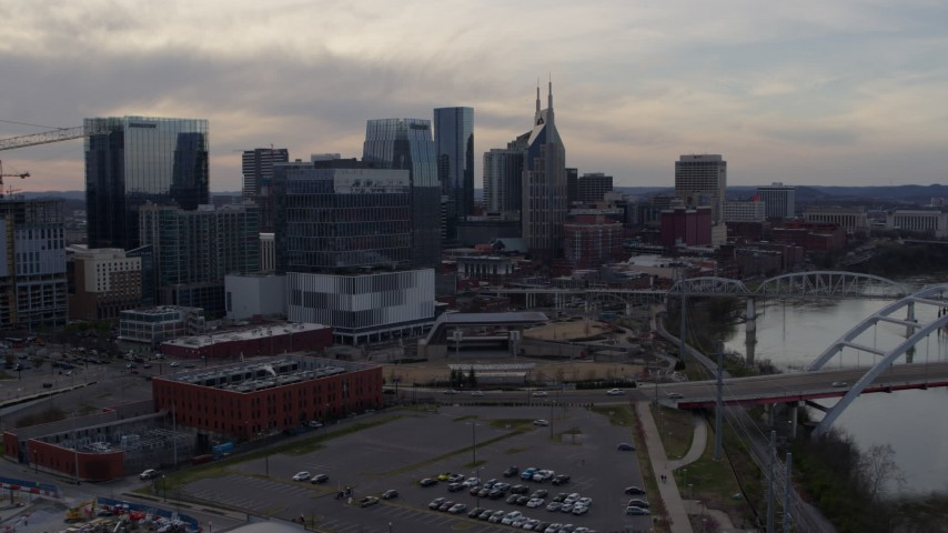 5.7K stock footage aerial video of flying away from city skyscrapers beside the river at sunset, Downtown Nashville, Tennessee Aerial Stock Footage | DX0002_119_037