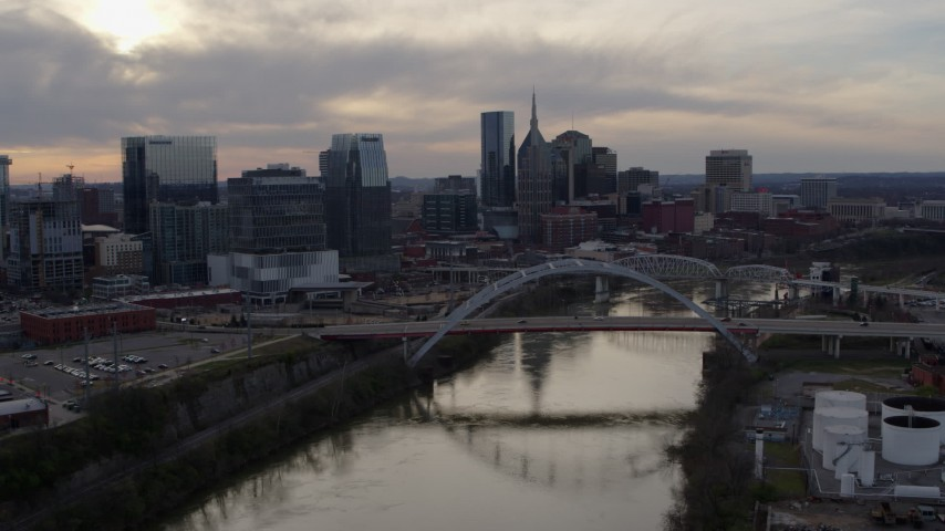 5.7K stock footage aerial video the city's skyline and bridges seen while passing the Cumberland River at sunset, Downtown Nashville, Tennessee Aerial Stock Footage | DX0002_119_038