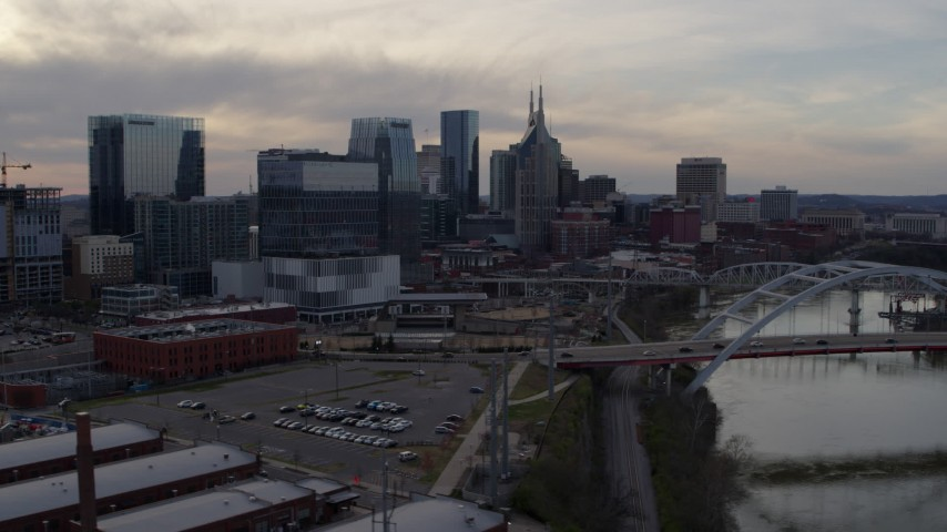 5.7K stock footage aerial video ascend past bridges and Cumberland River at sunset for view of skyscrapers, Downtown Nashville, Tennessee Aerial Stock Footage | DX0002_119_040
