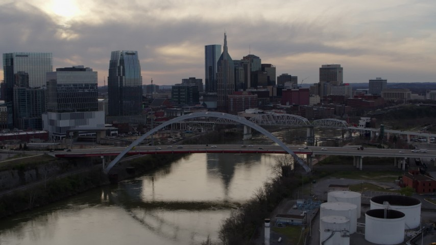 5.7K stock footage aerial video of the city skyline by bridges and Cumberland River at sunset, Downtown Nashville, Tennessee Aerial Stock Footage DX0002_119_042 | Axiom Images
