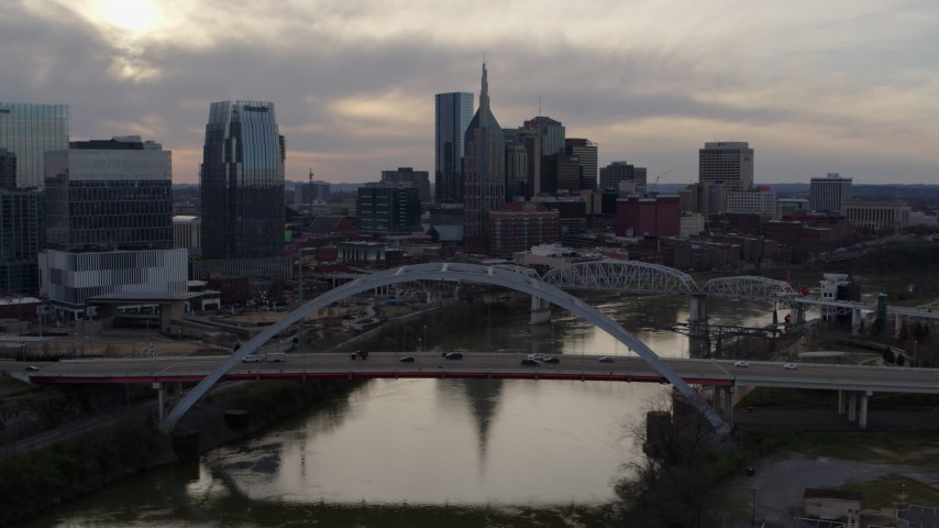 5.7K stock footage aerial video flying by the city skyline near bridges and Cumberland River at sunset, Downtown Nashville, Tennessee Aerial Stock Footage | DX0002_119_043