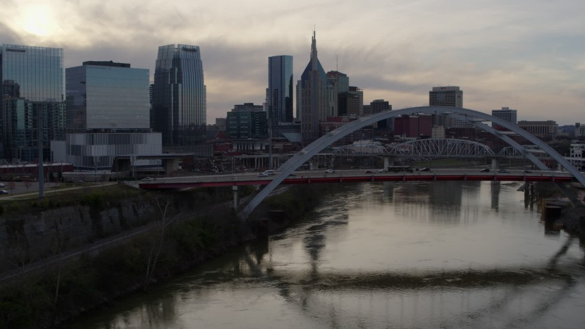 5.7K stock footage aerial video fly close to bridge on Cumberland River at sunset, skyline in background, Downtown Nashville, Tennessee Aerial Stock Footage | DX0002_119_044