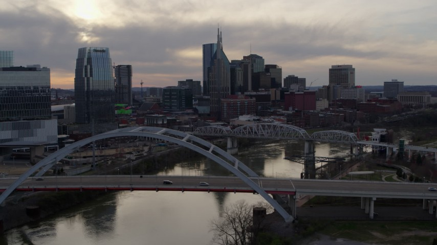 5.7K stock footage aerial video ascend past bridge on Cumberland River at sunset, skyline in background, Downtown Nashville, Tennessee Aerial Stock Footage | DX0002_119_045