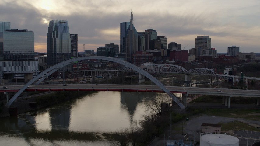 5.7K stock footage aerial video passing the bridge on Cumberland River at sunset, skyline behind it, Downtown Nashville, Tennessee Aerial Stock Footage | DX0002_119_046