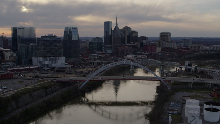 5.7K stock footage aerial video fly away from and past city skyline behind a bridge on Cumberland River at sunset, Downtown Nashville, Tennessee Aerial Stock Footage | DX0002_119_048