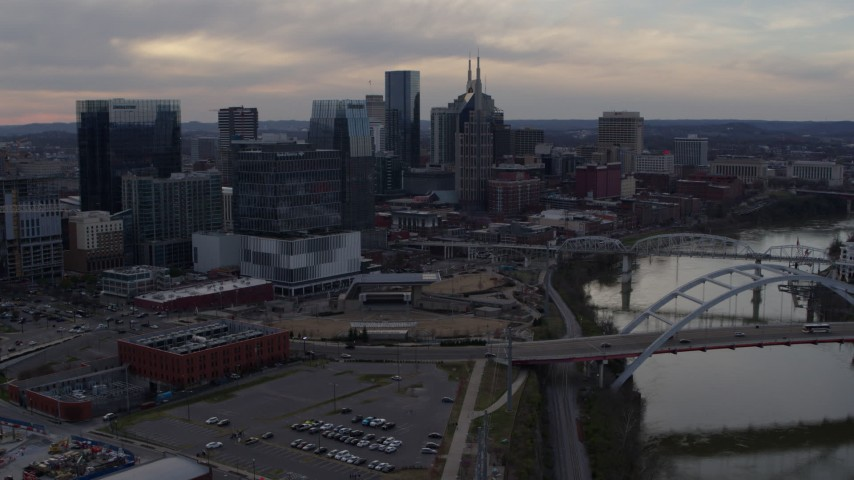 5.7K stock footage aerial video approach city skyline near a bridge on Cumberland River at sunset, and descend, Downtown Nashville, Tennessee Aerial Stock Footage | DX0002_119_049