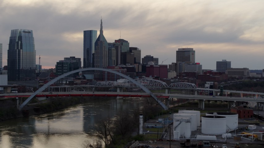 5.7K stock footage aerial video flying by riverfront skyline, bridge, and Cumberland River at sunset, Downtown Nashville, Tennessee Aerial Stock Footage | DX0002_120_004