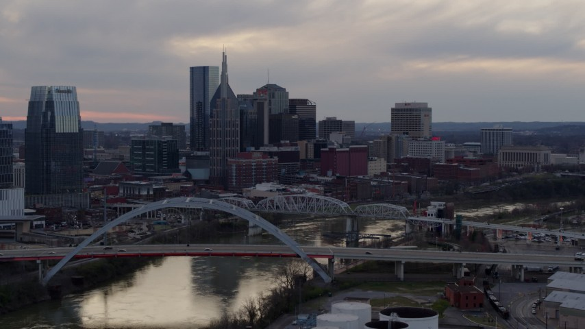 5.7K stock footage aerial video flying away from riverfront skyline, bridges, and the Cumberland River at sunset, Downtown Nashville, Tennessee Aerial Stock Footage | DX0002_120_007