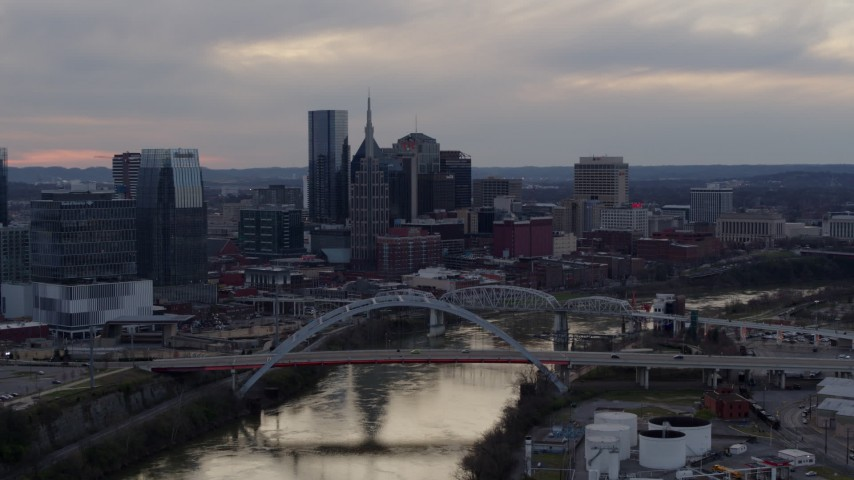 5.7K stock footage aerial video flying by the riverfront skyline and bridges spanning the Cumberland River at sunset, Downtown Nashville, Tennessee Aerial Stock Footage | DX0002_120_008