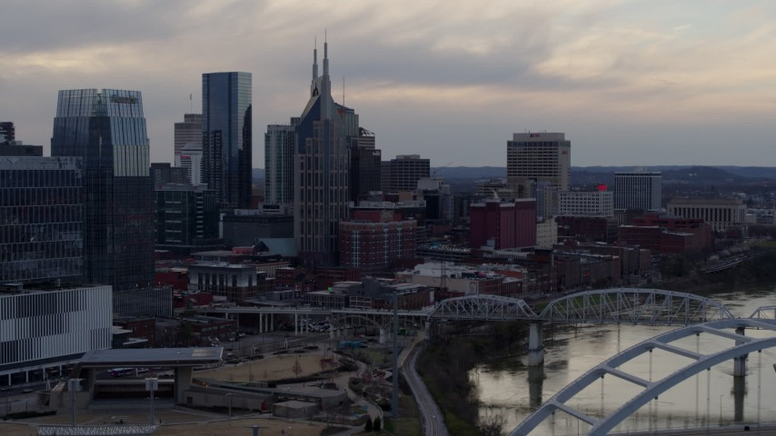 5.7K stock footage aerial video of the AT&T Building and neighboring buildings by the Cumberland River at sunset, Downtown Nashville, Tennessee Aerial Stock Footage | DX0002_120_010