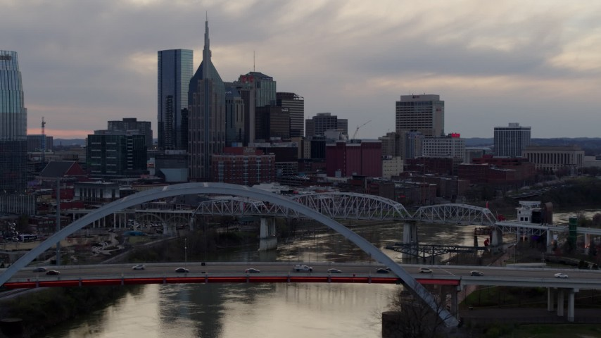 5.7K stock footage aerial video flying by the riverfront skyscrapers and bridges spanning the Cumberland River at sunset, Downtown Nashville, Tennessee Aerial Stock Footage | DX0002_120_011