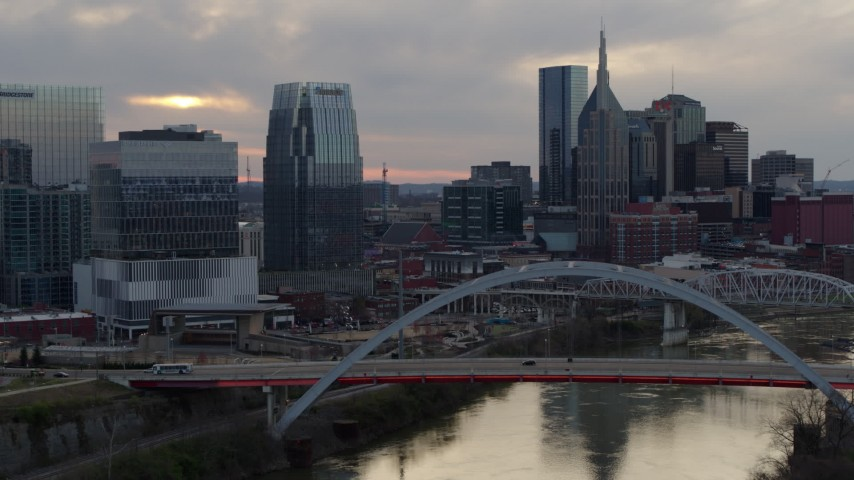 5.7K stock footage aerial video of the riverfront skyline, ascend past bridge spanning the river at sunset, Downtown Nashville, Tennessee Aerial Stock Footage | DX0002_120_012
