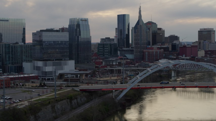 5.7K stock footage aerial video of the riverfront skyline while passing bridge spanning the river at sunset, Downtown Nashville, Tennessee Aerial Stock Footage | DX0002_120_013