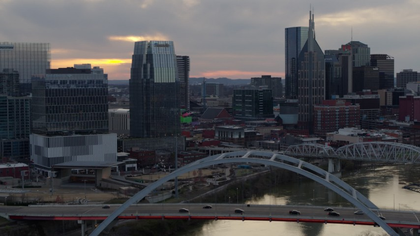 5.7K stock footage aerial video focus on a tall skyscraper while flying by a bridge on the river at sunset, Downtown Nashville, Tennessee Aerial Stock Footage | DX0002_120_015