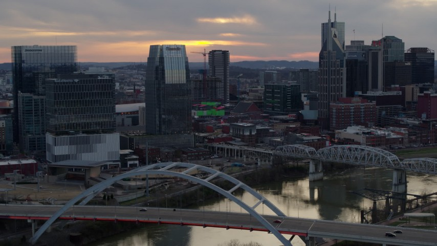 5.7K stock footage aerial video approach Pinnacle skyscraper and a bridge on the river at sunset, Downtown Nashville, Tennessee Aerial Stock Footage | DX0002_120_017