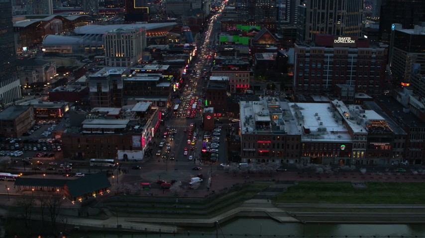 5.7K stock footage aerial video of orbiting Broadway, crowded with cars, at twilight, Downtown Nashville, Tennessee Aerial Stock Footage DX0002_120_023