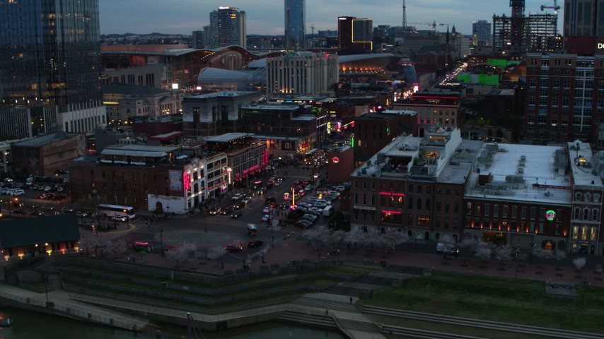 5.7K stock footage aerial video of orbiting Broadway, crowded with cars and pedestrians, at twilight, Downtown Nashville, Tennessee Aerial Stock Footage | DX0002_120_024
