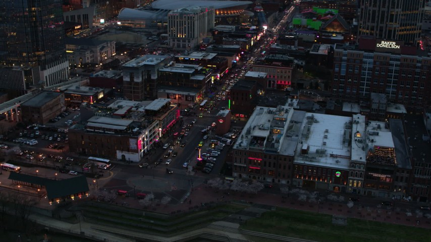 5.7K stock footage aerial video orbiting buildings, cars and pedestrians around Broadway at twilight, Downtown Nashville, Tennessee Aerial Stock Footage | DX0002_120_025