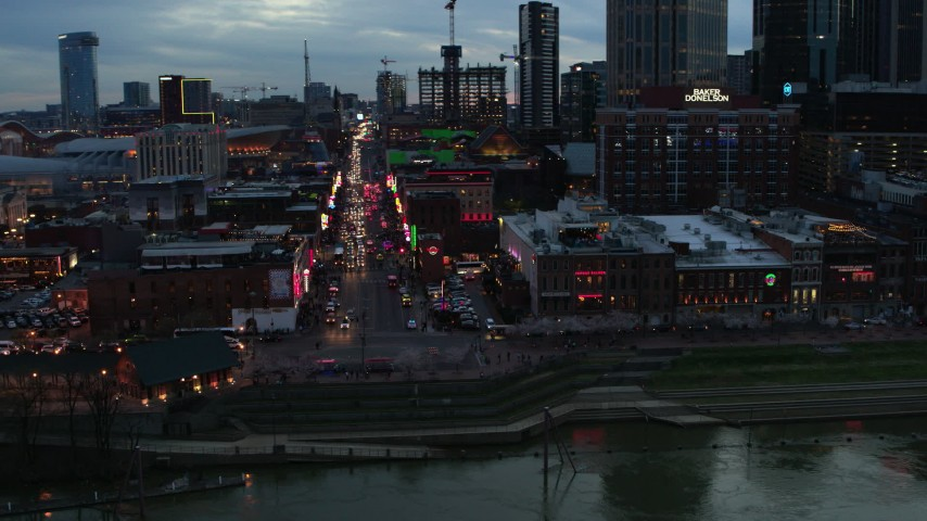 5.7K stock footage aerial video of circling buildings, cars and pedestrians around Broadway at twilight, Downtown Nashville, Tennessee Aerial Stock Footage | DX0002_120_027