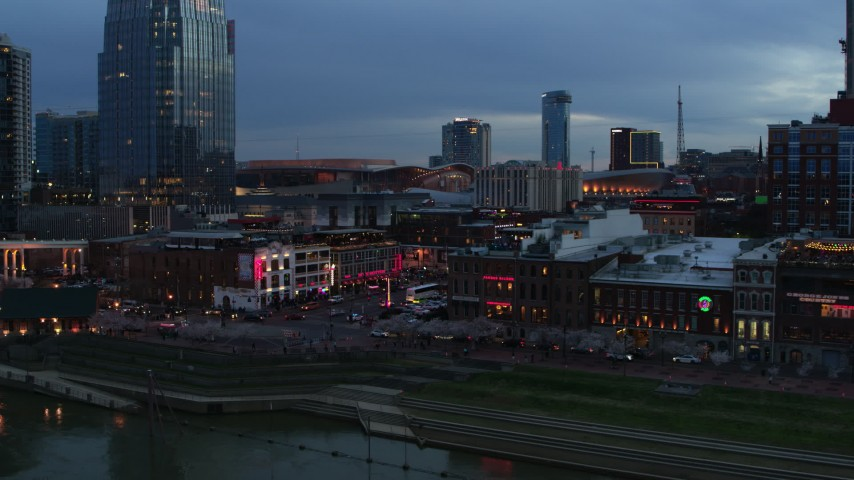 5.7K stock footage aerial video approach riverfront buildings, cars on Broadway at twilight, Downtown Nashville, Tennessee Aerial Stock Footage | DX0002_120_028