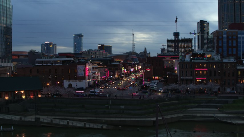 5.7K stock footage aerial video descend and flyby riverfront buildings, cars on Broadway at twilight, Downtown Nashville, Tennessee Aerial Stock Footage | DX0002_120_029