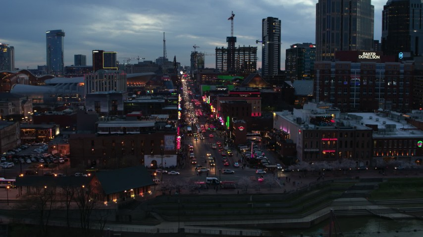 5.7K stock footage aerial video of riverfront buildings, cars on Broadway at twilight during ascent, Downtown Nashville, Tennessee Aerial Stock Footage | DX0002_120_030