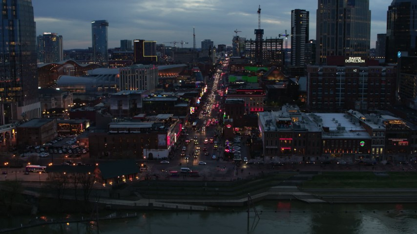 5.7K stock footage aerial video reverse view of riverfront buildings, cars on Broadway at twilight, Downtown Nashville, Tennessee Aerial Stock Footage | DX0002_120_031