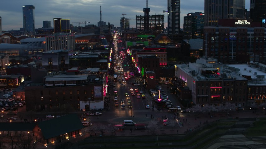 5.7K stock footage aerial video flying toward traffic and pedestrians on Broadway at twilight, Downtown Nashville, Tennessee Aerial Stock Footage | DX0002_120_032