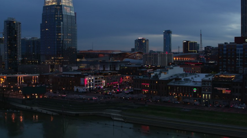 5.7K stock footage aerial video fly away from traffic and riverfront buildings at the end of Broadway at twilight, Downtown Nashville, Tennessee Aerial Stock Footage | DX0002_120_034
