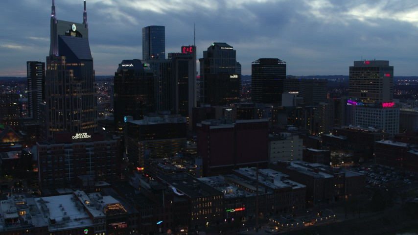 5.7K stock footage aerial video ascend while flying by tall skyscrapers near AT&T Building at twilight, Downtown Nashville, Tennessee Aerial Stock Footage | DX0002_120_035