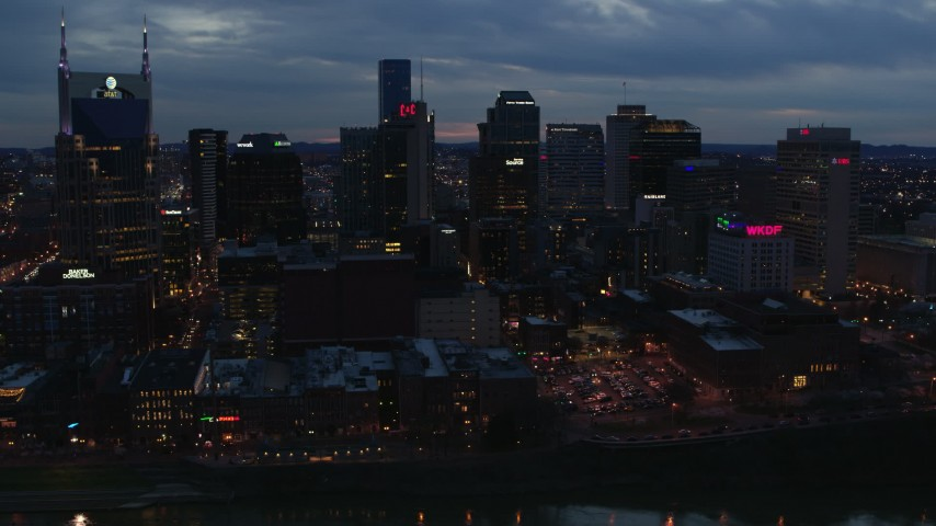 5.7K stock footage aerial video passing by a group of skyscrapers at twilight before approach, Downtown Nashville, Tennessee Aerial Stock Footage | DX0002_120_039