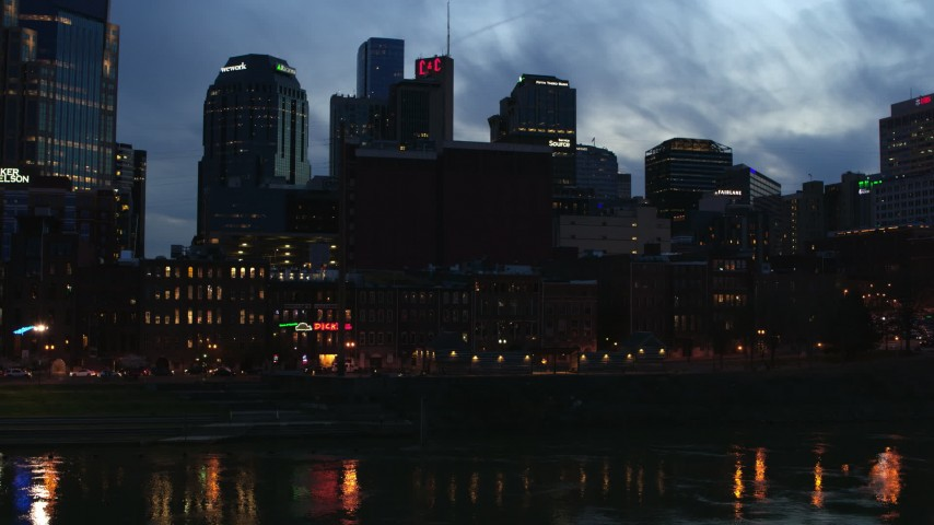 5.7K stock footage aerial video of a group of skyscrapers at twilight while descending toward the river, Downtown Nashville, Tennessee Aerial Stock Footage | DX0002_120_041