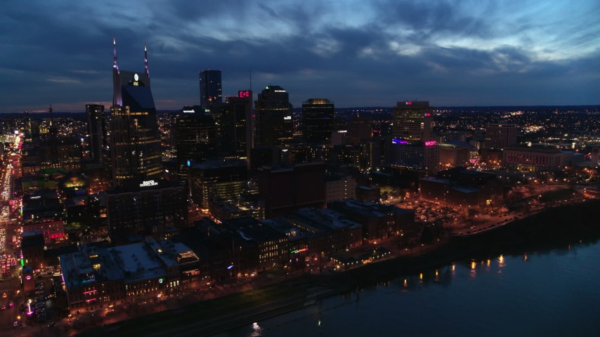 5.7K stock footage aerial video of crossing the river toward the city's skyline at twilight, Downtown Nashville, Tennessee Aerial Stock Footage | DX0002_121_004