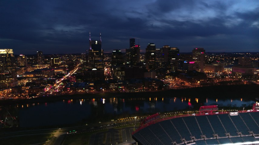 5.7K stock footage aerial video reverse view of city's skyline and river, seen from stadium at twilight, Downtown Nashville, Tennessee Aerial Stock Footage | DX0002_121_009