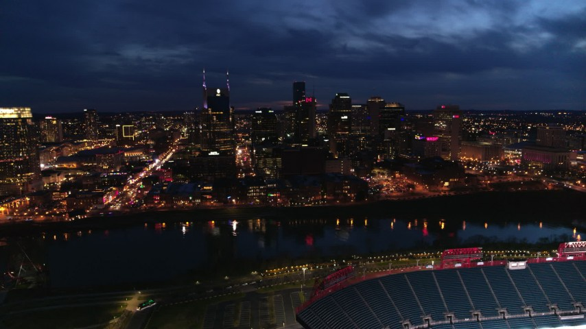 5.7K stock footage aerial video approach the city's skyline and river from stadium at twilight, Downtown Nashville, Tennessee Aerial Stock Footage | DX0002_121_010