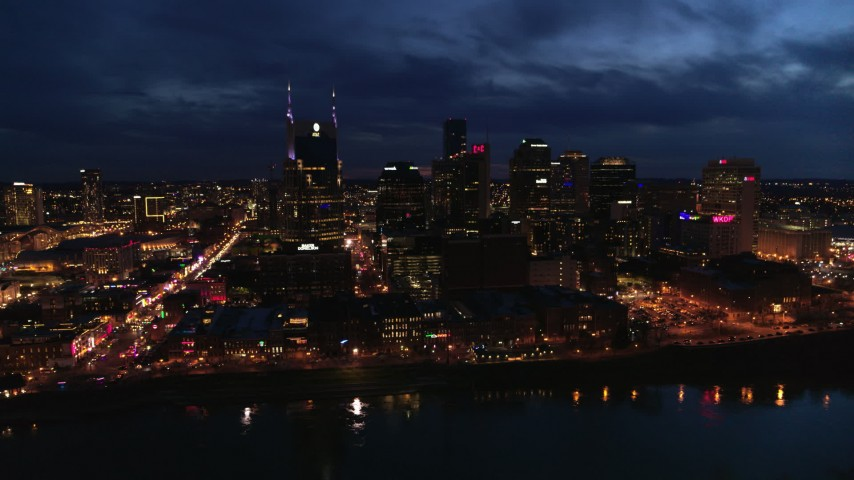 5.7K stock footage aerial video flying away from the AT&T Building and skyline at twilight, reveal the river, Downtown Nashville, Tennessee Aerial Stock Footage | DX0002_121_013