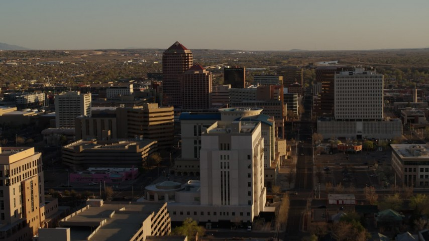 5.7K stock footage aerial video descend near courthouse, fly away from office high-rises in Downtown Albuquerque, New Mexico Aerial Stock Footage DX0002_122_030 | Axiom Images
