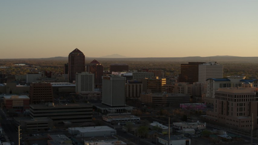 5.7K stock footage aerial video fly away from high-rise office buildings at sunset and ascend past Downtown Albuquerque, New Mexico Aerial Stock Footage | DX0002_122_034