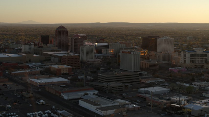 5.7K stock footage aerial video of descending past high-rise office buildings at sunset, Downtown Albuquerque, New Mexico Aerial Stock Footage | DX0002_122_035