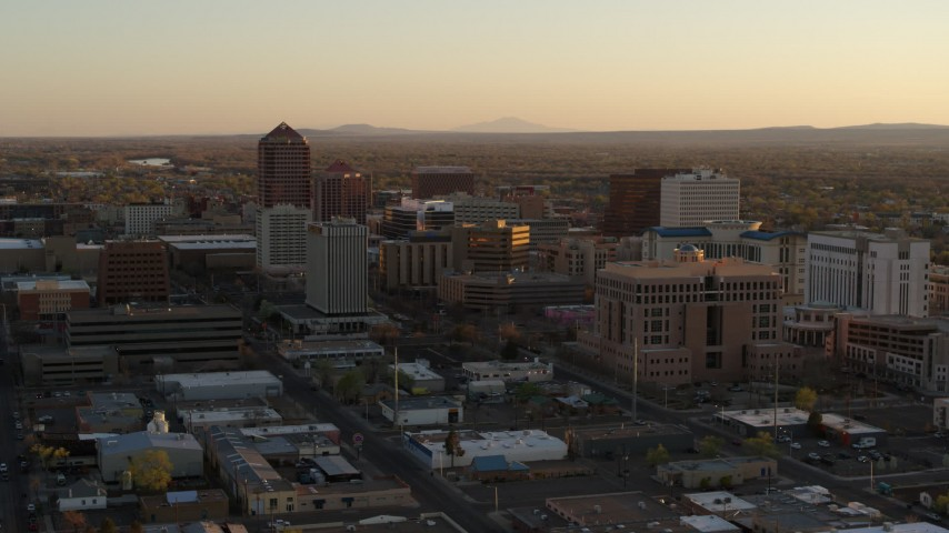 5.7K stock footage aerial video of a reverse view of high-rise office buildings at sunset and ascend, Downtown Albuquerque, New Mexico Aerial Stock Footage | DX0002_122_042