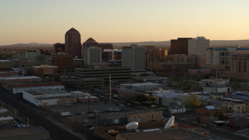 5.7K stock footage aerial video fly away from office high-rises at sunset during descent, Downtown Albuquerque, New Mexico Aerial Stock Footage | DX0002_122_046