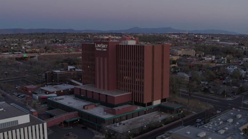 5.7K stock footage aerial video of a reverse view of a hospital at sunset in Albuquerque, New Mexico Aerial Stock Footage DX0002_123_002 | Axiom Images