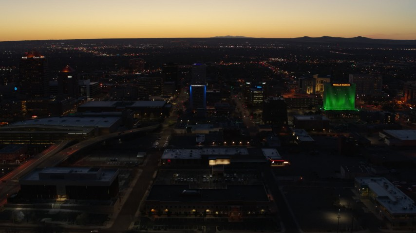 5.7K stock footage aerial video ascend and orbit DoubleTree hotel with blue lighting near office buildings at twilight, Downtown Albuquerque, New Mexico Aerial Stock Footage | DX0002_123_032